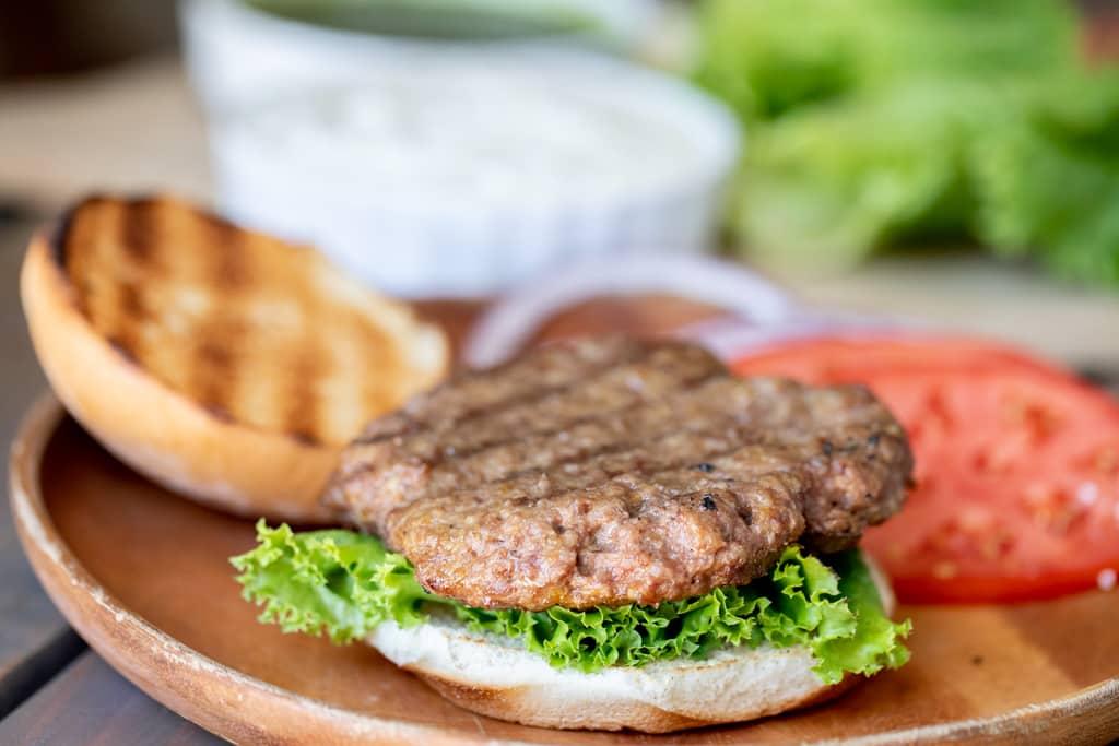Curry lamb burger patty on a lettuce leaf and burger bun.