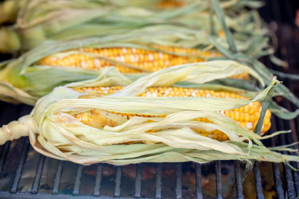 Seasoned corn in the husks on the grill grates of a smoker.