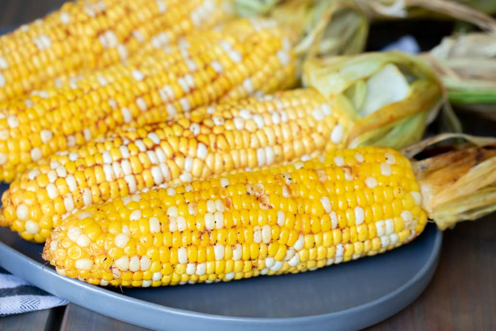Four ears of smoked corn on the cob on a gray plate.