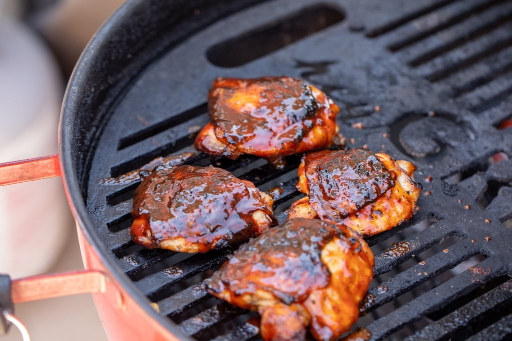 Sauced chicken thighs on the grill grates of a charcoal grill.