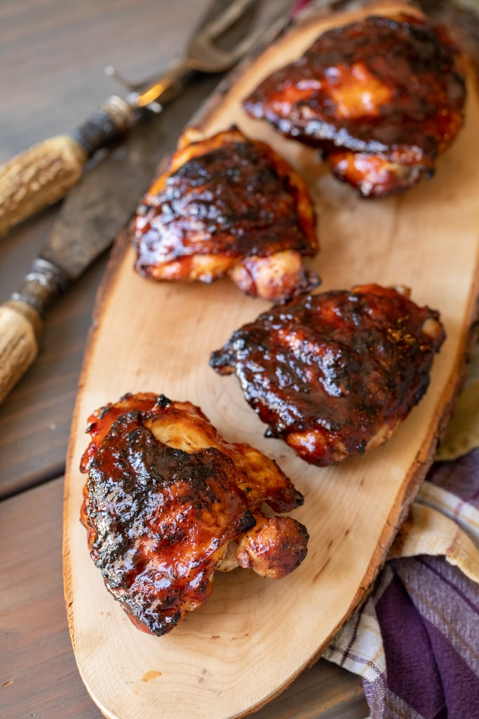 Four BBQ chicken thighs on a long, wooden cutting board.