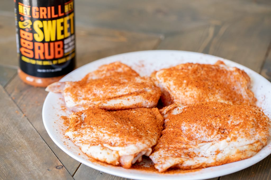 Four seasoned chicken thighs next to a bottle of Sweet Rub.