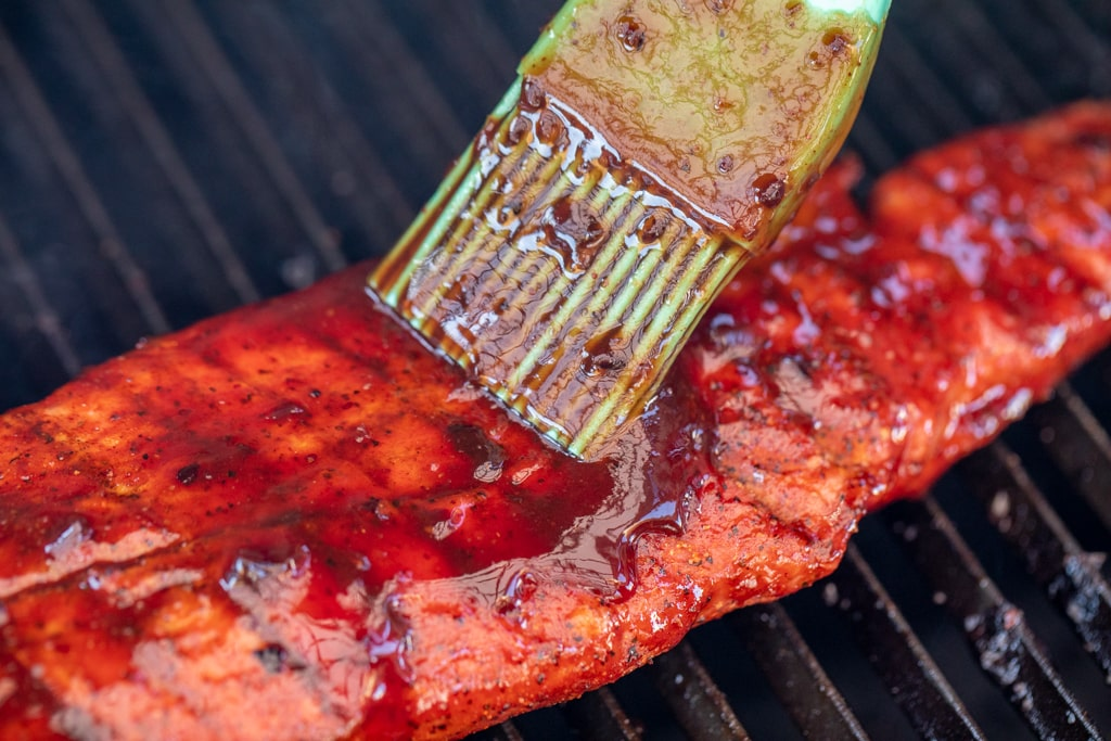 Blueberry BBQ Sauce being brushed on a pork tenderloin.