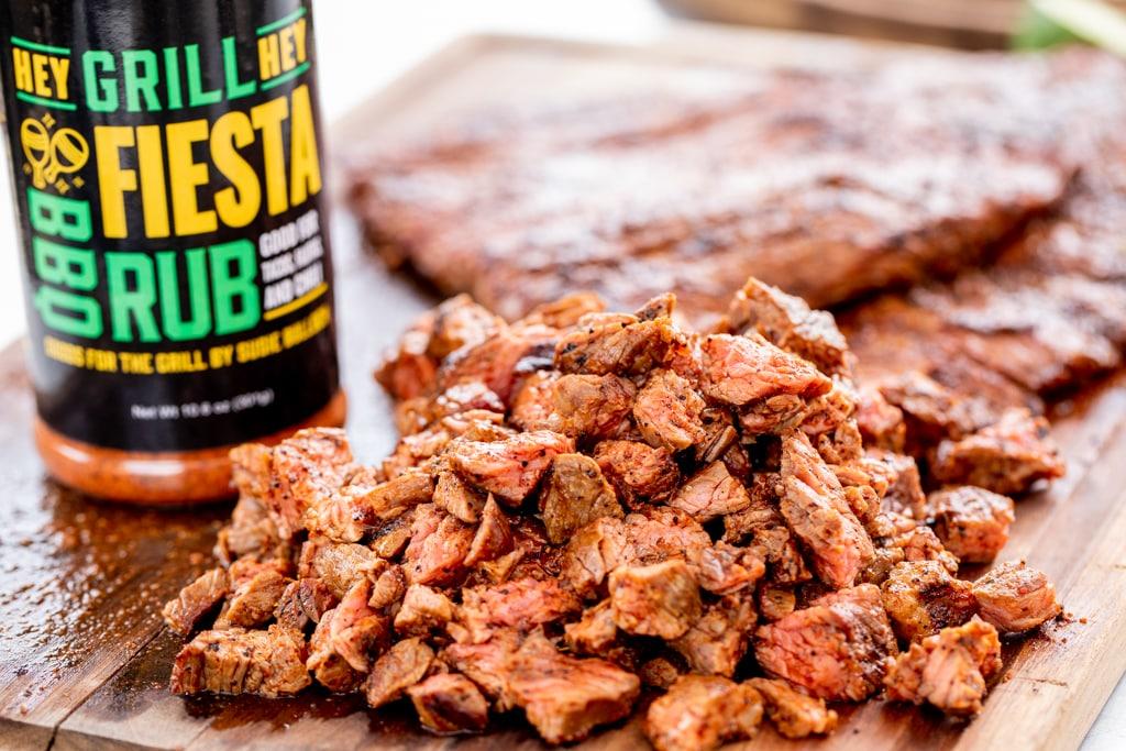 Chopped carne asada on a wooden cutting board next to a bottle of Hey Grill Hey Fiesta Rub