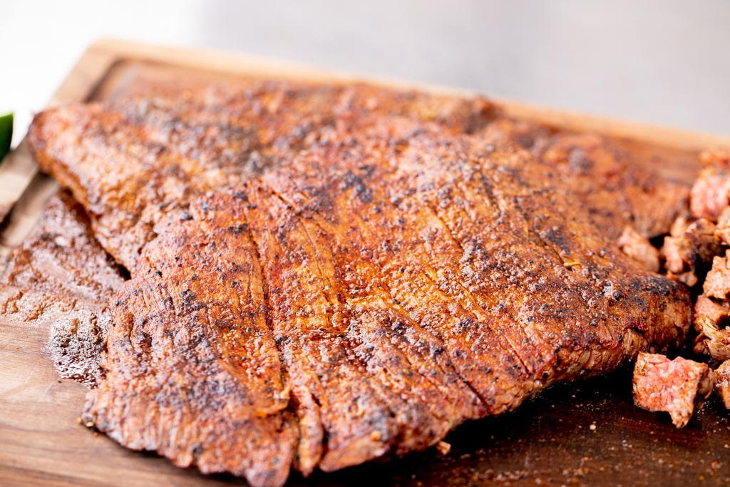 Seasoned carne asada flap steak on a wooden cutting board.