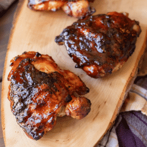 BBQ chicken thighs on a long, wooden cutting board.