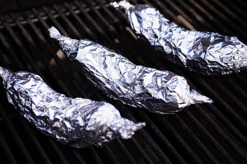 Bananas wrapped in aluminum foil on the grill.