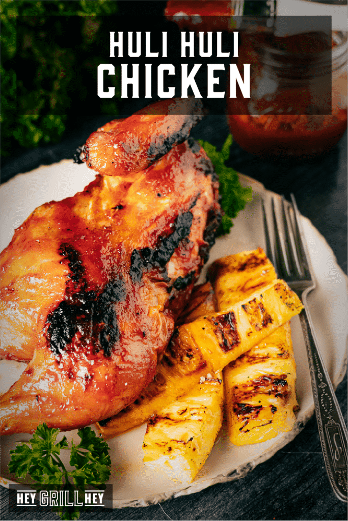 Huli huli chicken on a white plate next to grilled pineapple spears with text overlay - Huli Huli Chicken.
