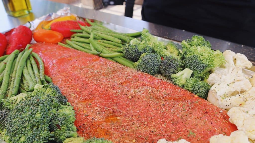 Seasoned uncooked salmon and vegetables on a sheet pan.