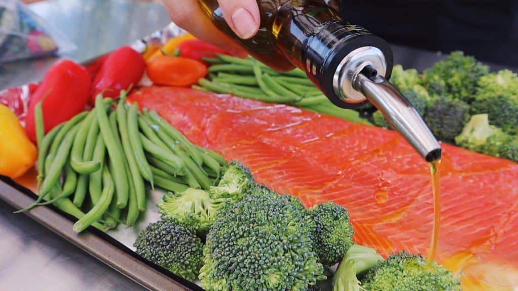 Olive oil being drizzled on a salmon fillet, broccoli, green beans, and peppers on a sheet pan.