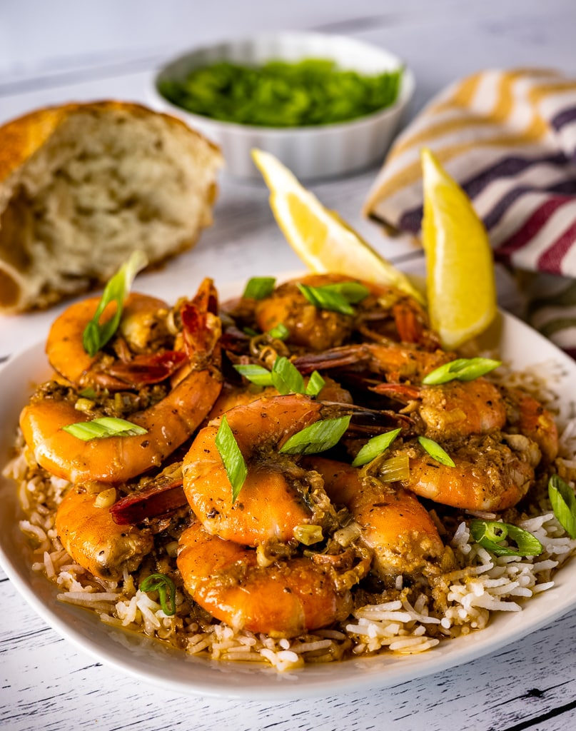 New Orleans BBQ shrimp over a bed of rice garnished with sliced onions and lemon wedges.