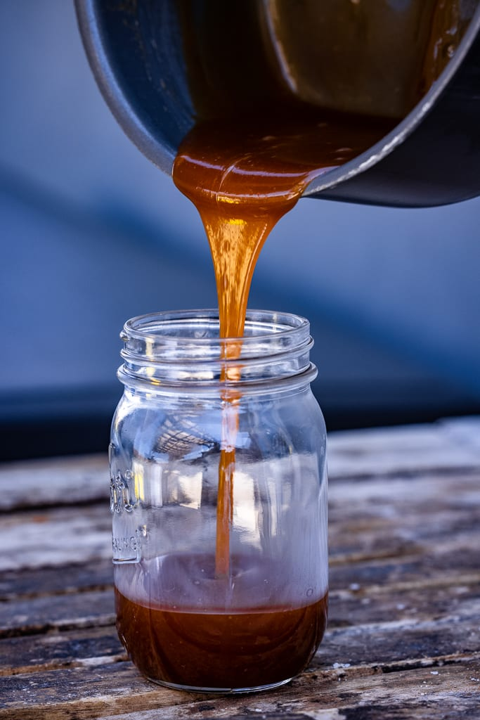Apple bourbon sauce being poured into a mason jar.