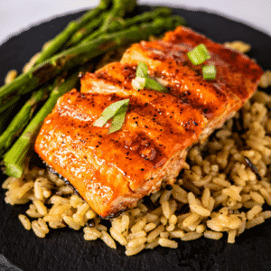 BBQ salmon on a bed of rice next to grilled asparagus.