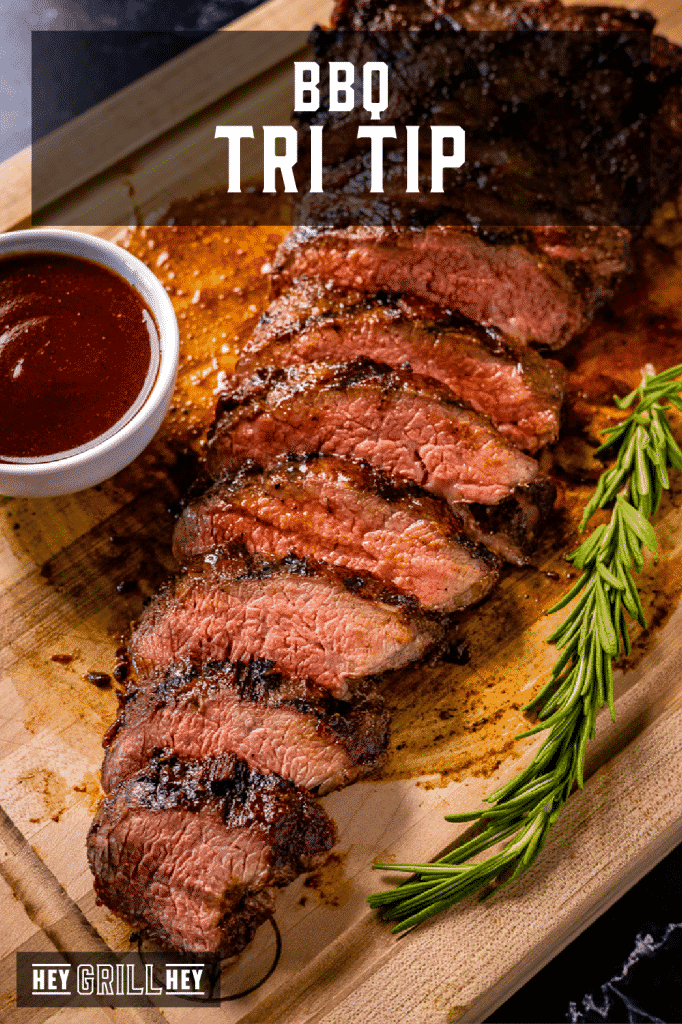 Sliced BBQ tri tip on a wooden cutting board with text overlay - BBQ Tri Tip.