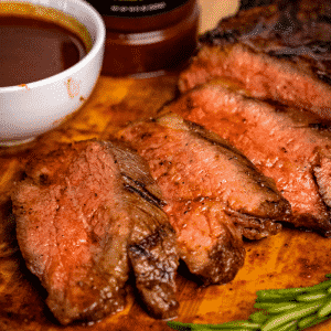 Sliced BBQ tri tip next to a small bowl of BBQ sauce.