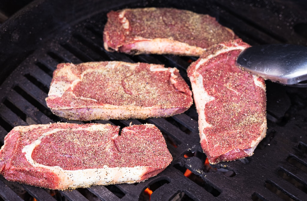 Four seasoned bison ribeye steaks on the grill grates of a charcoal grill.