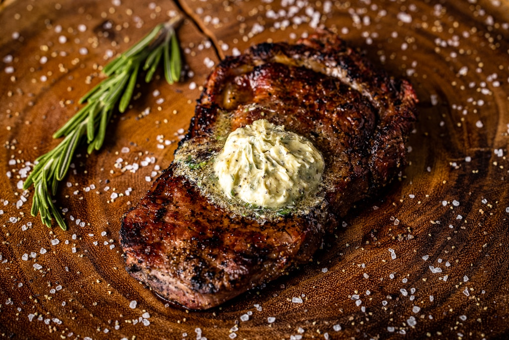 Grilled bison steak topped with resting steak butter on a wooden cutting board.