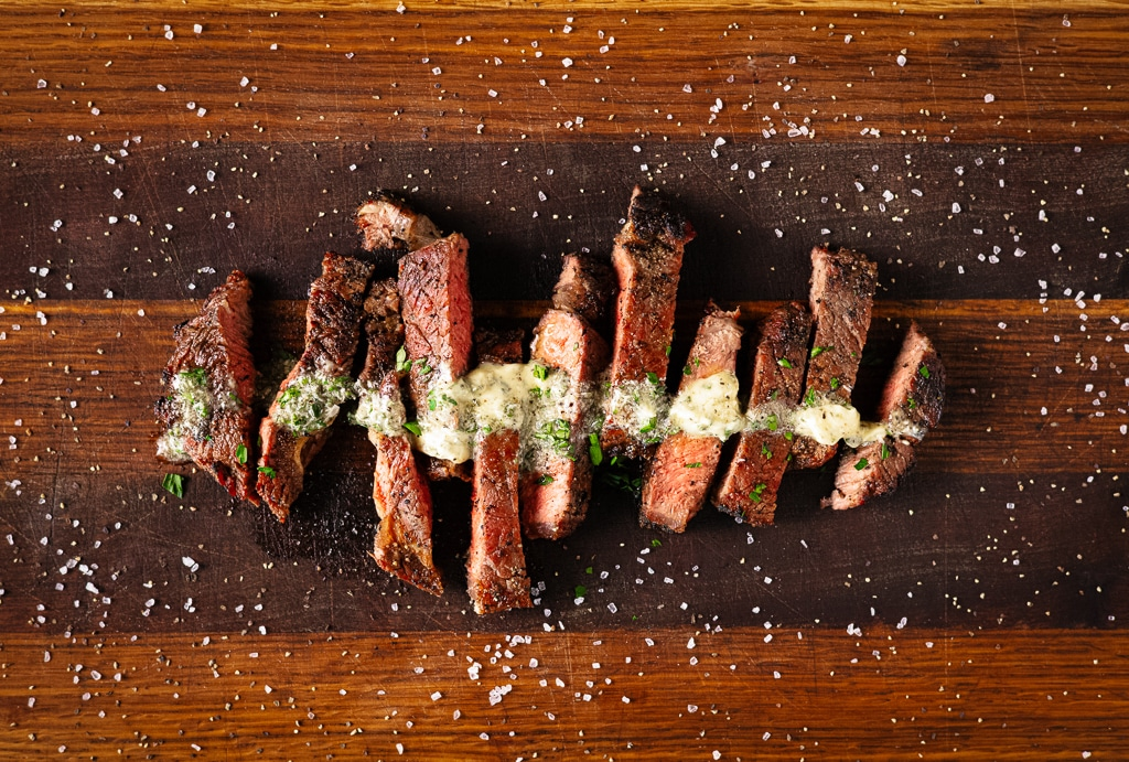 Sliced grilled bison steak topped with resting butter on a wooden cutting board.