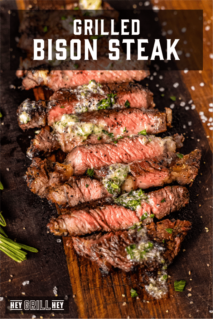 Sliced grilled bison steak topped with resting butter on a wooden cutting board with text overlay - Grilled Bison Steak.