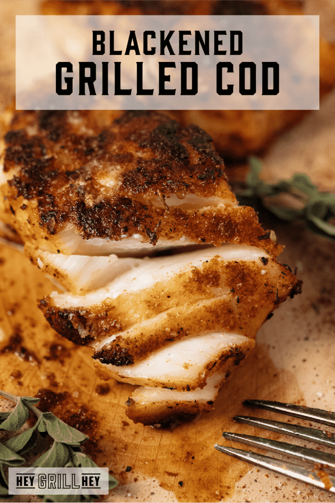 Flaked blackened grilled cod on a wooden cutting board with text overlay - Blackened Grilled Cod.