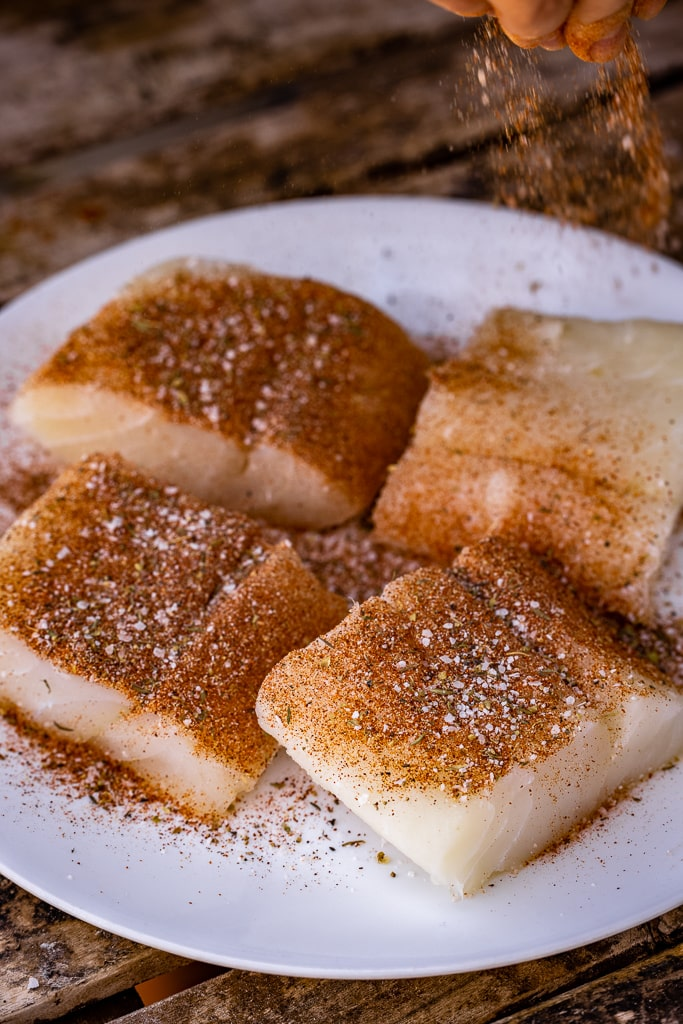 Four cod fillets being sprinkled with blackened seasoning on a large white plate.