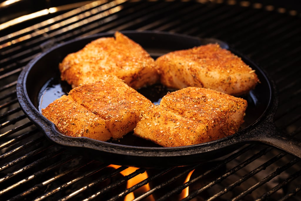 Four seasoned cod fillets in a cast iron skillet on the grill.