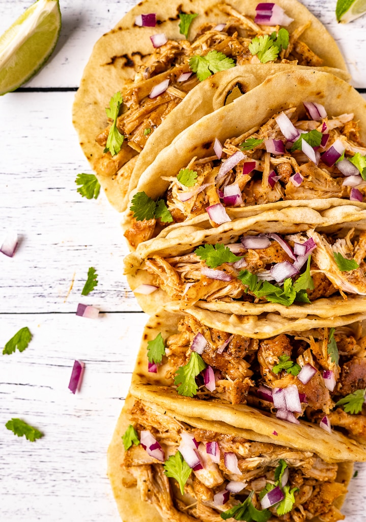 Chicken carnitas tacos in a row on a white wooden surface.