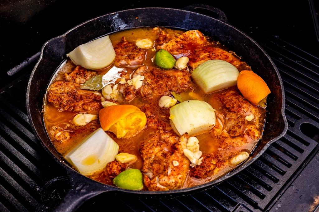 Seasoned chicken, lime, orange, and seasonings in a cast iron skillet.