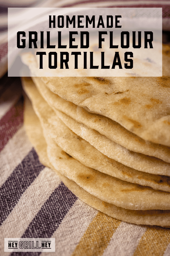 Stack of grilled flour tortillas on a striped dish towel with text overlay - Homemade Grilled Flour Tortillas.