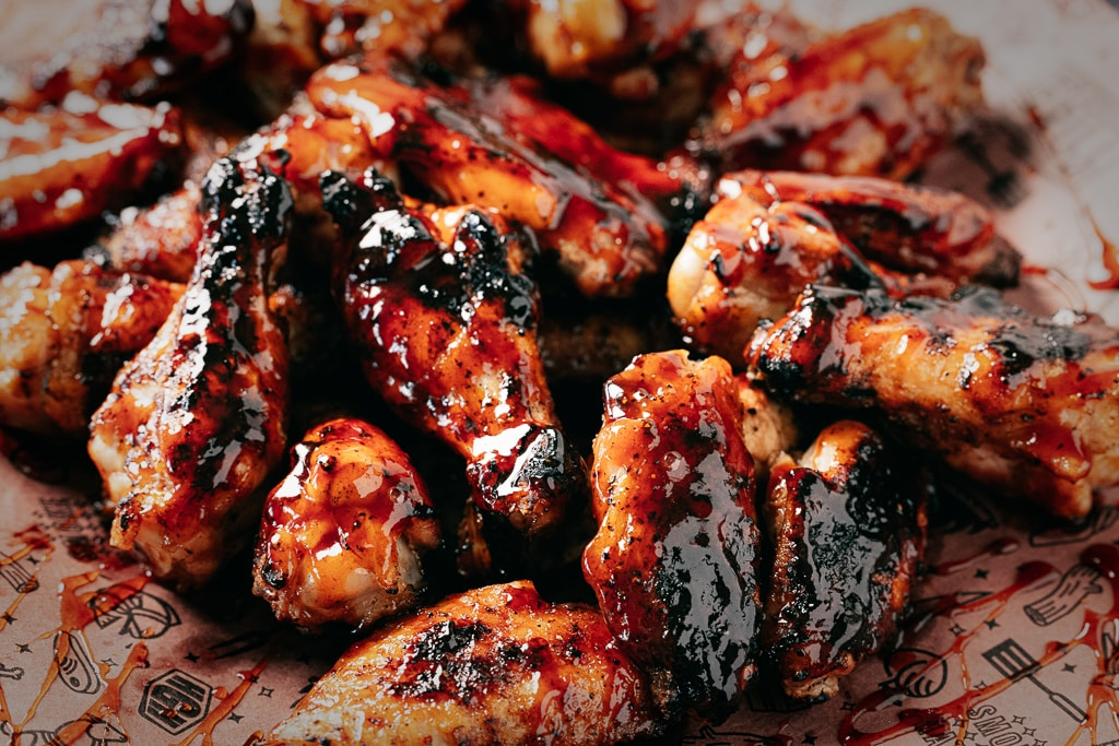 Honey BBQ chicken wings on top of peach butcher paper.