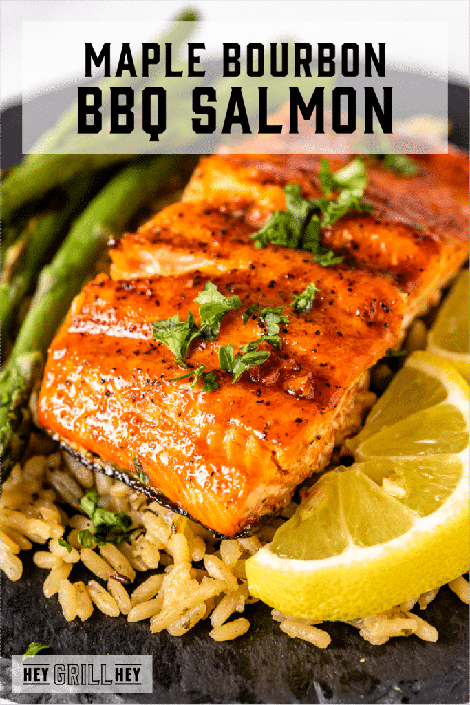 BBQ salmon on a bed of rice next to grilled asparagus with text overlay - Maple Bourbon BBQ Salmon.