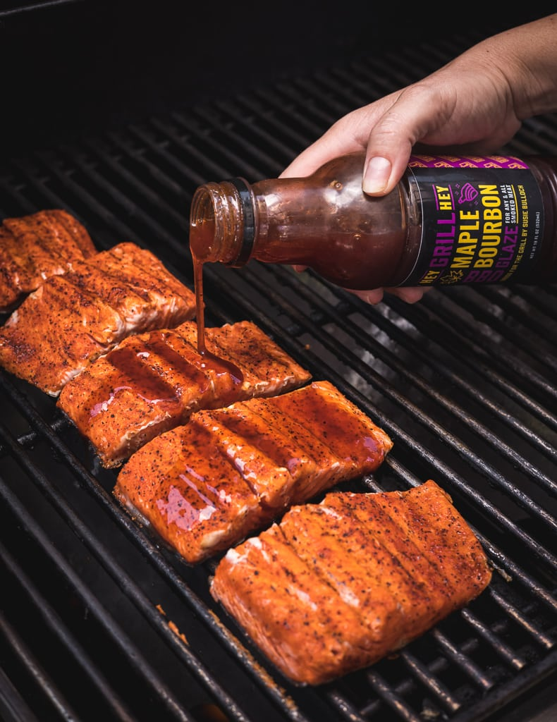 Maple bourbon grilling glaze being drizzled on salmon fillets on the grill.