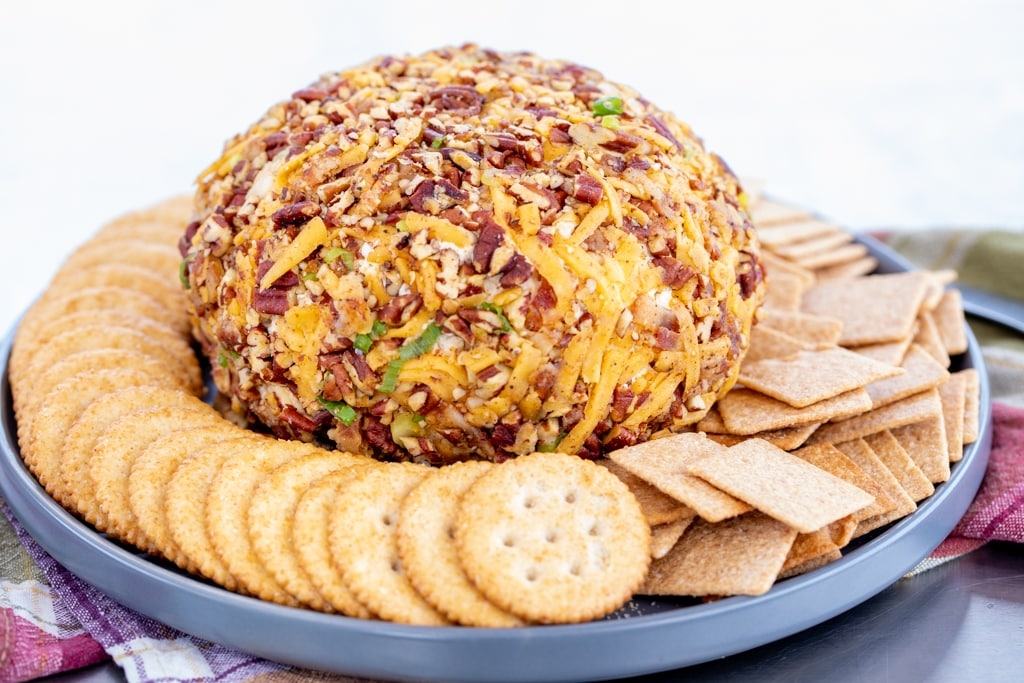 Smoked cream cheese ball surrounded by various crackers.