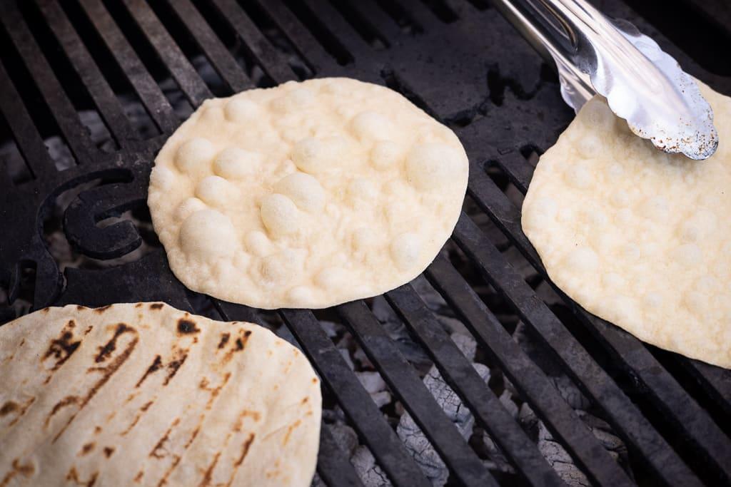 Three flour tortillas on a grill.