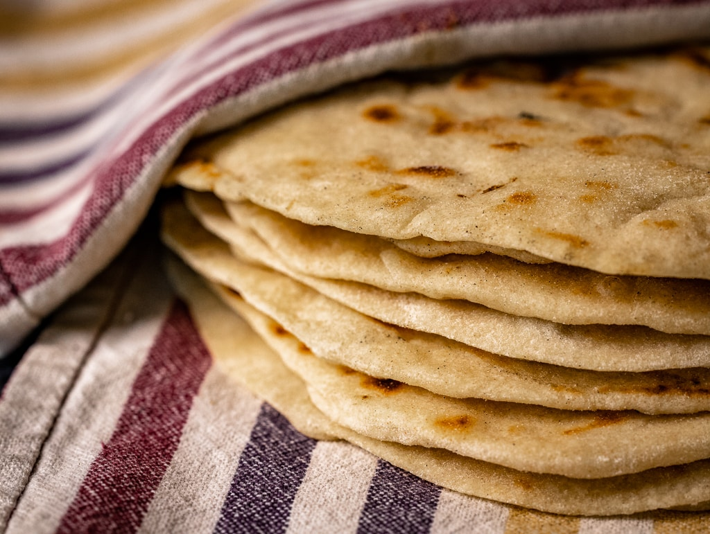 Stack of grilled flour tortillas on a striped dish towel.