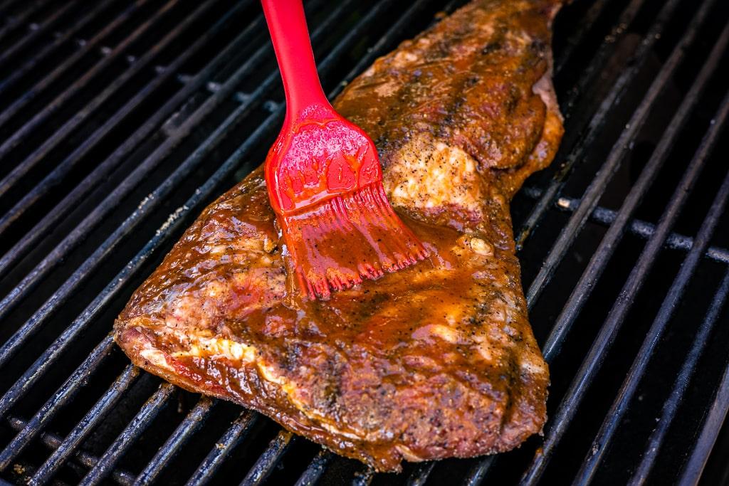 BBQ sauce being basted on a tri tip roast.