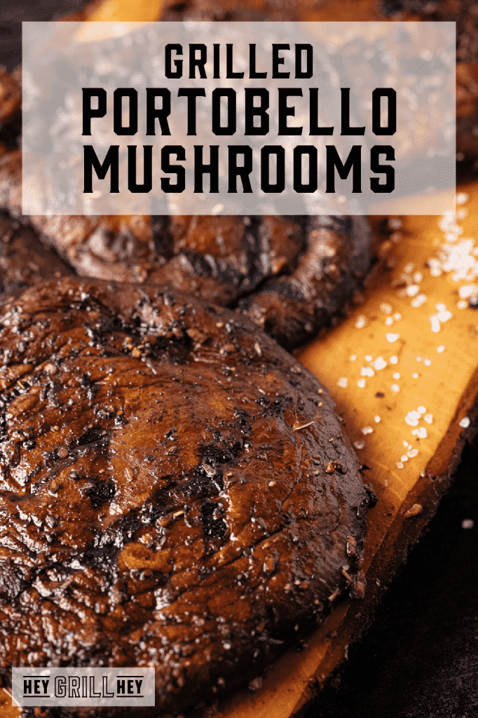 Three grilled portobello mushrooms on a wooden cutting board with text overlay - Grilled Portobello Mushrooms.