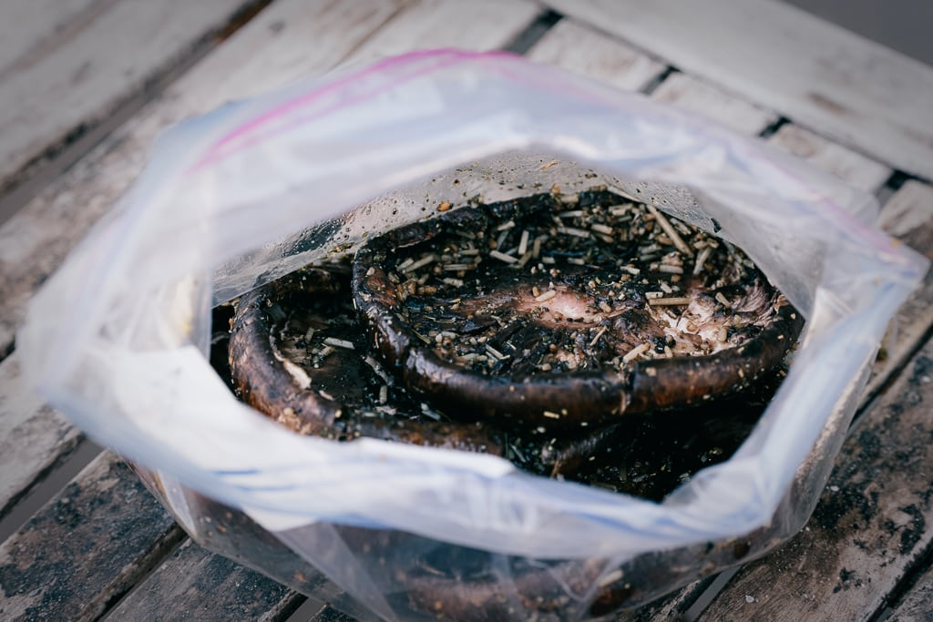 Portobello mushrooms in a zip-top bag filled with balsamic marinade.