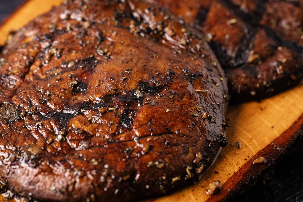 Two marinated and grilled portobello mushrooms on a wooden serving platter.